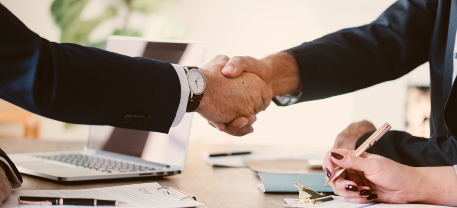 dos personas dándose la mano en una reunión